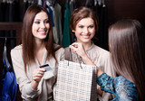 Pretty women pay charges account with credit card at the shop
