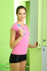 Young girl in locker room with bottle of water