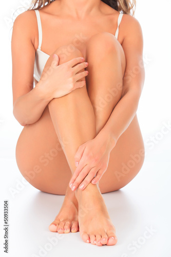Woman sitting on the floor touches leg by hand