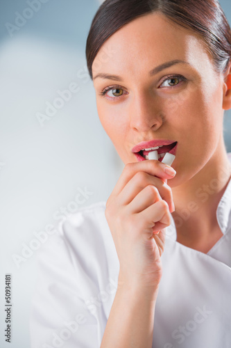 Young female dentist doctor holding chewing gum and smiling. Den