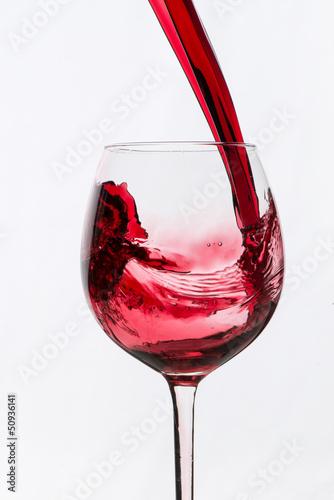 Ein Glas Rotwein eingiessen