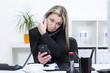 Überforderte Frau im Büro mit mehreren Telefonen
