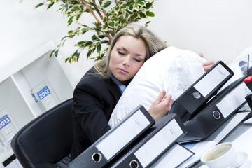 Angestellte schläft mit Kopfkissen auf dem Schreibtisch
