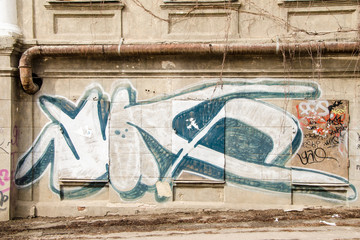 Indigo graffiti on concrete wall of old building