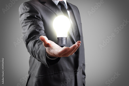 Light bulb in hand of businessman