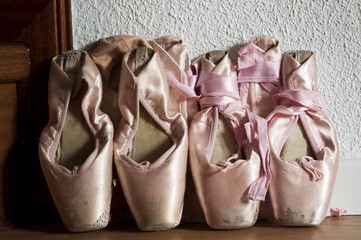 Group of pointe shoes leaned against the wall