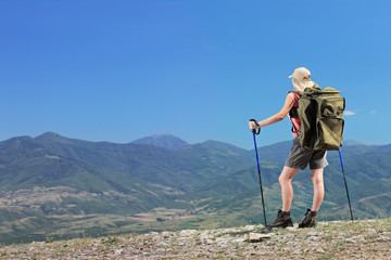 Woman with backpacki hiking a mountain
