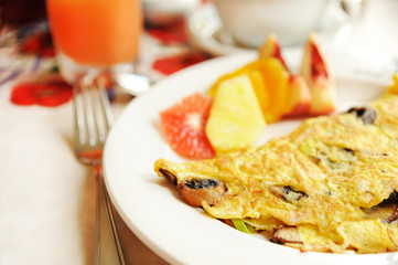 Omelet with mushrooms served with fruits - vegetarian breakfast
