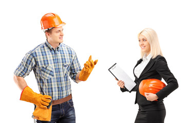 Male manual worker having a conversation with female architect