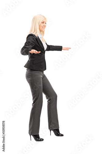Full length portrait of a businesswoman trying to keep balance