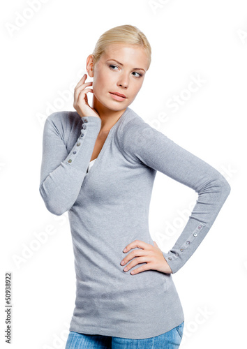 Woman in grey pullover admiring herself, isolated on white