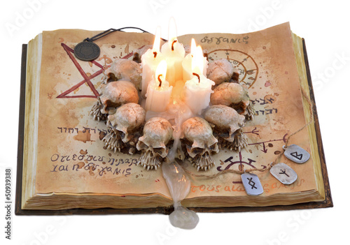 Magic book isolated with candle