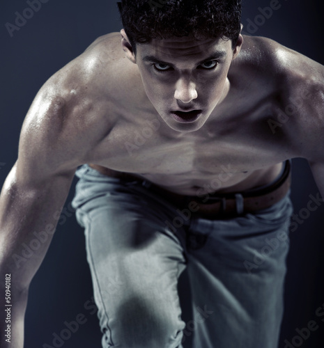 Serious muscular young man preapring to run