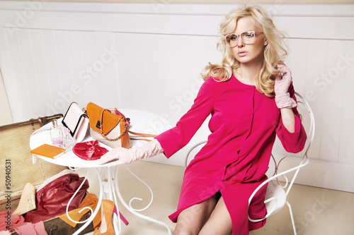 Stylish blonde lady in room full off fashion elements