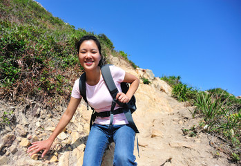 woman hiker climbing on mountain rock