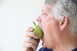 senior man eats a fresh pear