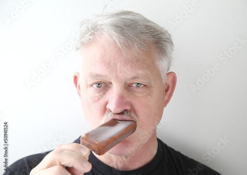 man eats chocolate ice cream bar