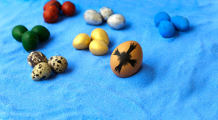 colorful eggs and cross on blue sand background