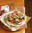 Wheat flat bread with chard leaves, cherry tomatoes