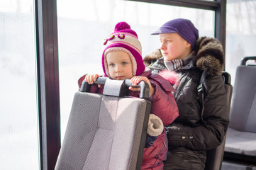 Adorable girl with mother ride on modern city bus in sunny winte