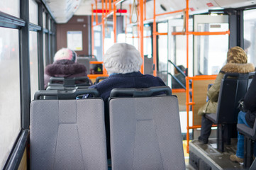 Interior of front side of modern city bus with passengers and or