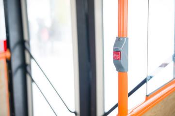 Stop alert button on orange handle in modern city bus