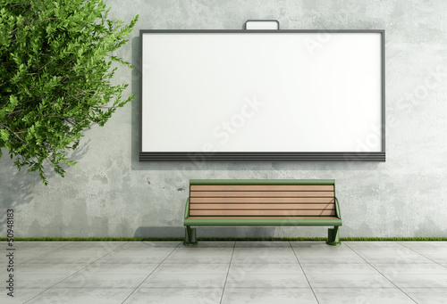 Advertising street bilboard on grunge wall with bench