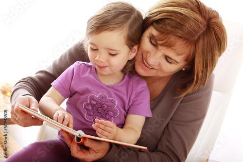 Eine Oma liest ihrer Enkeltochter aus einem Buch vor