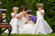 Bride stand with little girls in elegant dresses