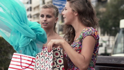 Girlfriends checking shoppings in city, super slow motion