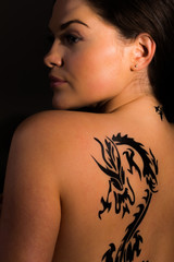 Sexy female model with dragon tattoo on her back