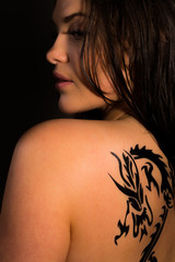 Beautiful female with tribal dragon tattoo