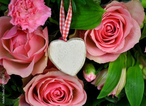 Weißes Holzherz zwischen Rosen