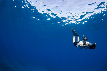 A free diver swims with underwater camera