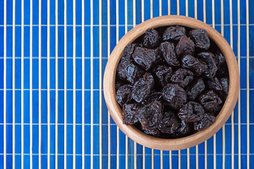 Dried prunes in wooden bowl
