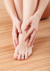 Beautiful female hands and feet on wooden floor
