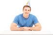 A smiling birthday guy with a party hat posing