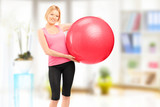 Blond female athlete holding a pilates ball and posing indoor