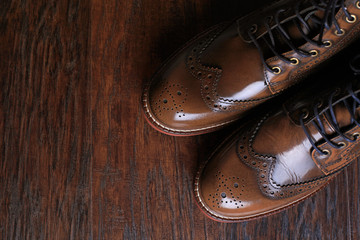 luxury brown shoes on wood background.