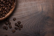 coffee beans and wooden bowl on brown table
