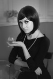 Retro styled woman with glass of cognac, black and white