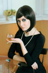 Retro styled woman with glass of cognac sitting at table