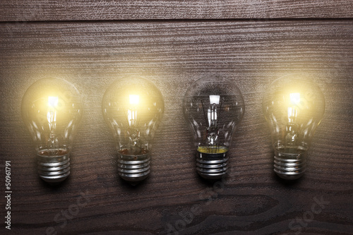 glowing bulbs weak link concept on wooden background