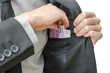 Putting banknotes in a jacket pocket