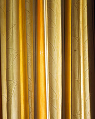 dense yellow textile curtain background with folds