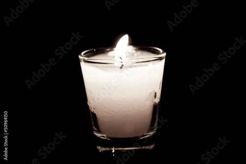 candle in glass on black background
