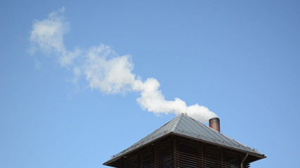 white smoke vapour rise house roof chimney blue sky