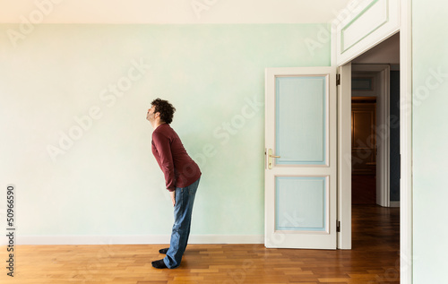 portrait of a weird guy in a room with the door open