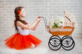 Girl in orange skirt with vintage pram