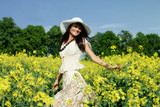 Young woman in the yellow rape field